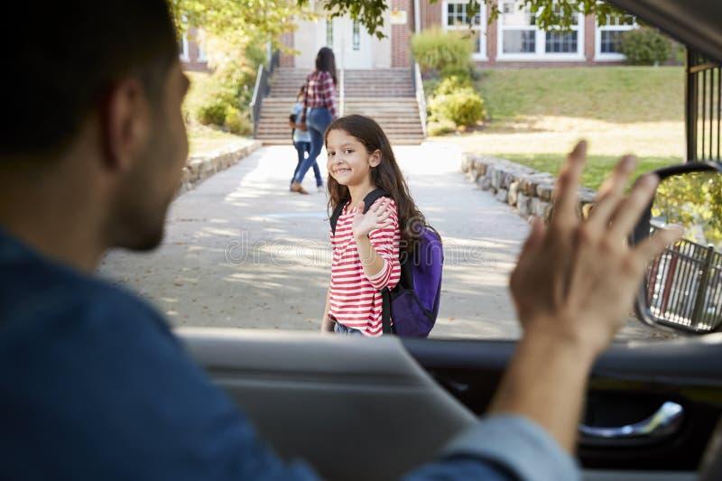 滴下在学校门前面的女儿的汽车的父亲 库存照片