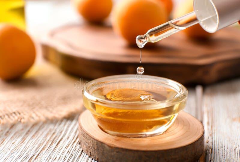 滴下的杏子精油到在桌上的碗里 免版税库存图片