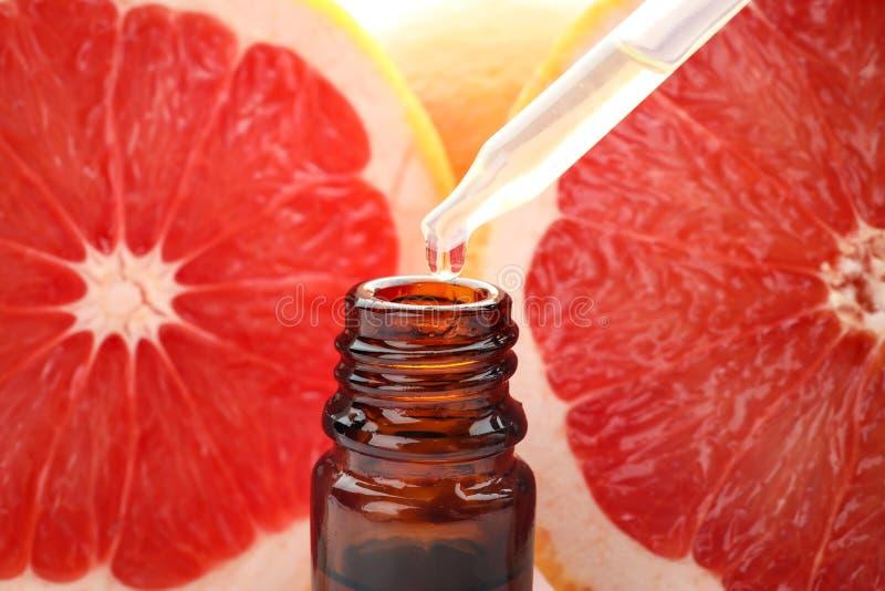 滴下的柑橘精油到瓶,特写镜头里 免版税库存照片