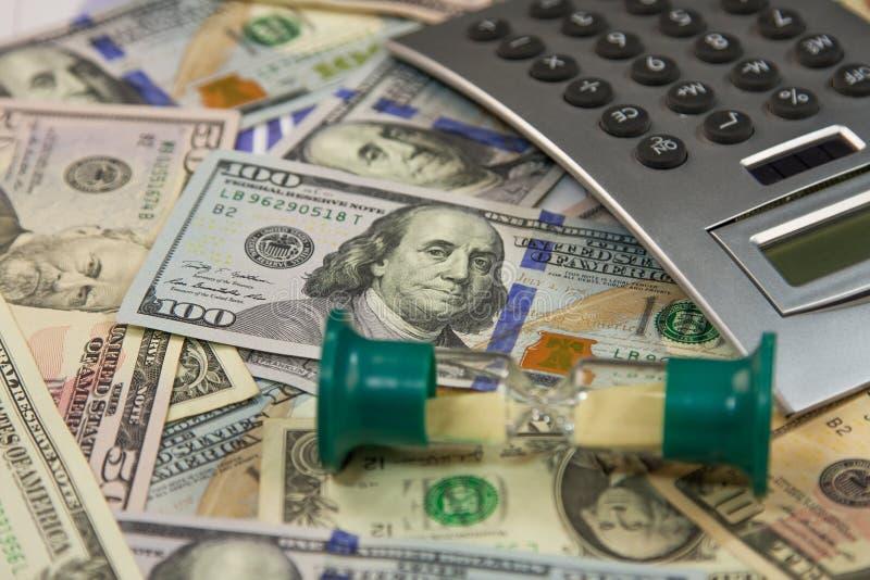 滴漏在美元在金钱背景的钞票和计算器谎言 企业和财务概念 免版税图库摄影