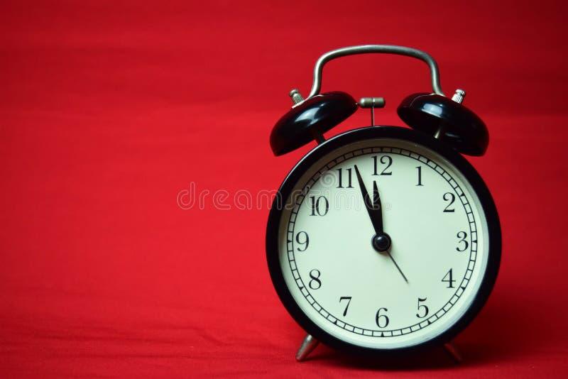 滴答作响对在红色背景的12点的时钟 图库摄影