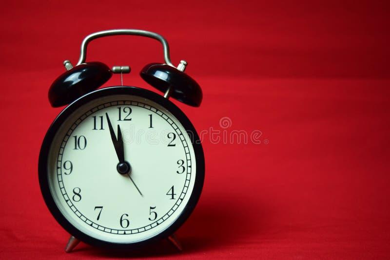 滴答作响对在红色背景的12点的时钟 库存图片
