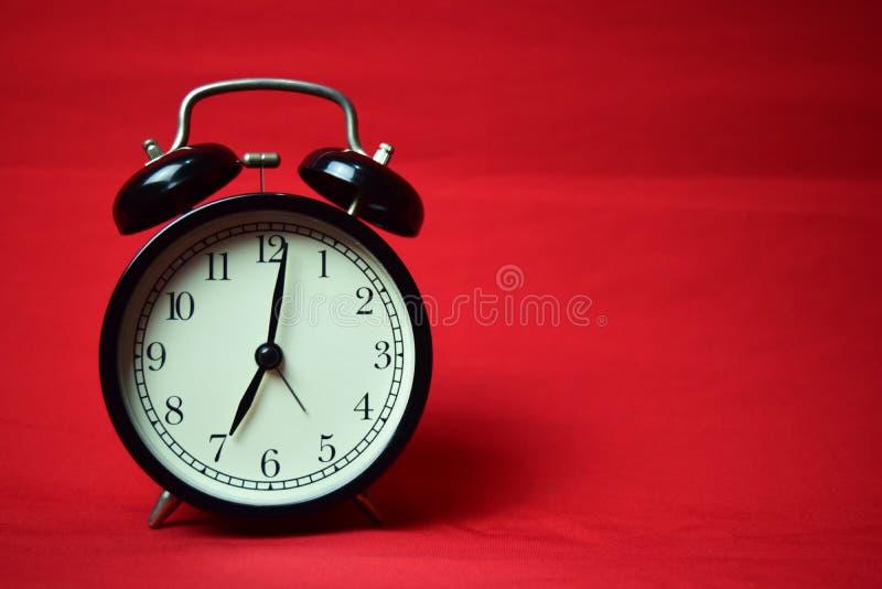 滴答作响对在红色背景的7点的时钟 免版税库存图片