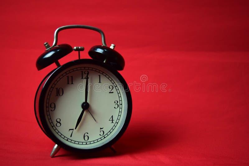滴答作响对在红色背景的7点的时钟 库存图片