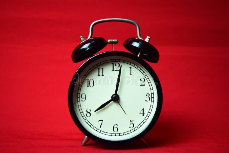 滴答作响对在红色背景的8点的时钟 免版税库存照片