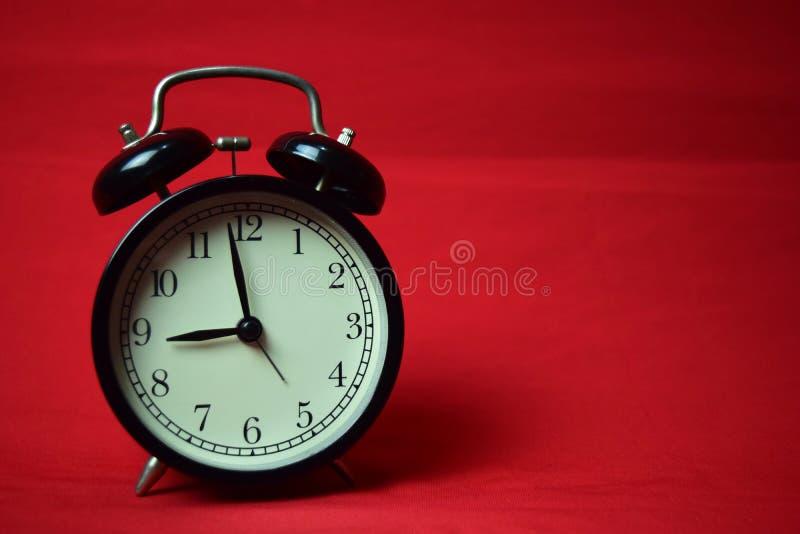 滴答作响对在红色背景的9点的时钟 免版税库存图片