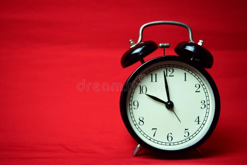 滴答作响对在红色背景的10点的时钟 免版税库存图片