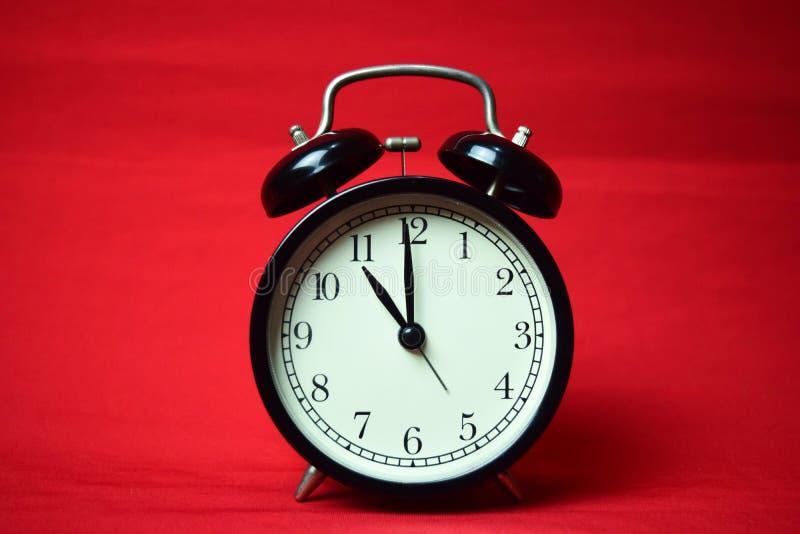 滴答作响对在红色背景的11点的时钟 免版税库存图片