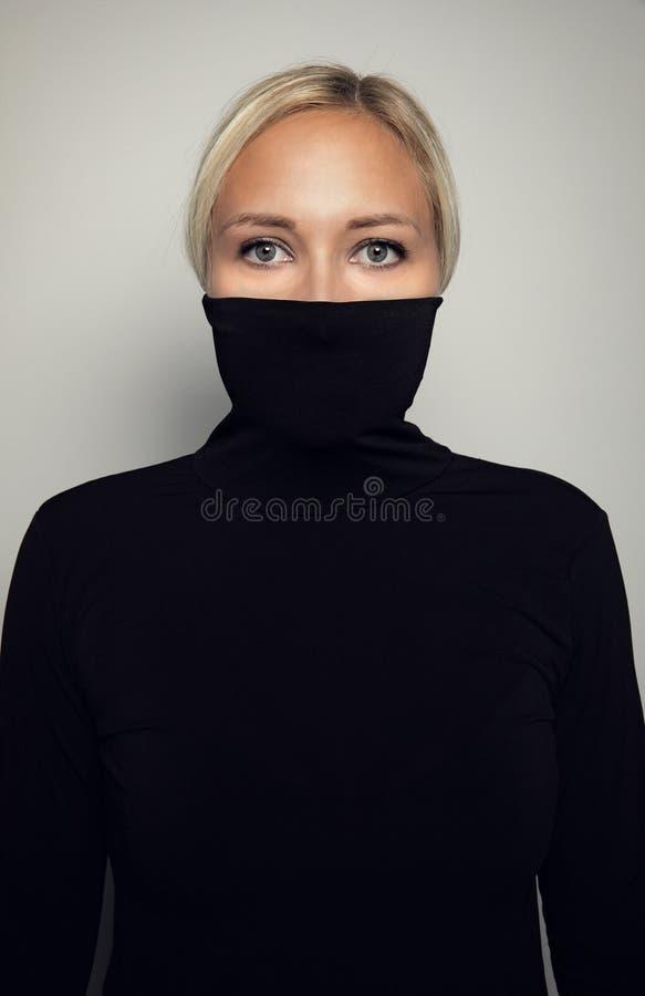 漂亮优雅女性的工作室肖像,用黑色高领衫保护她的脸 库存照片