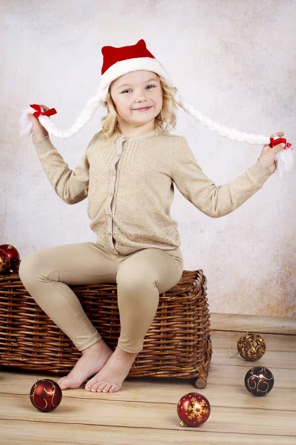 漂亮的孩子佩带的圣诞节盖帽坐柳条 免版税库存图片