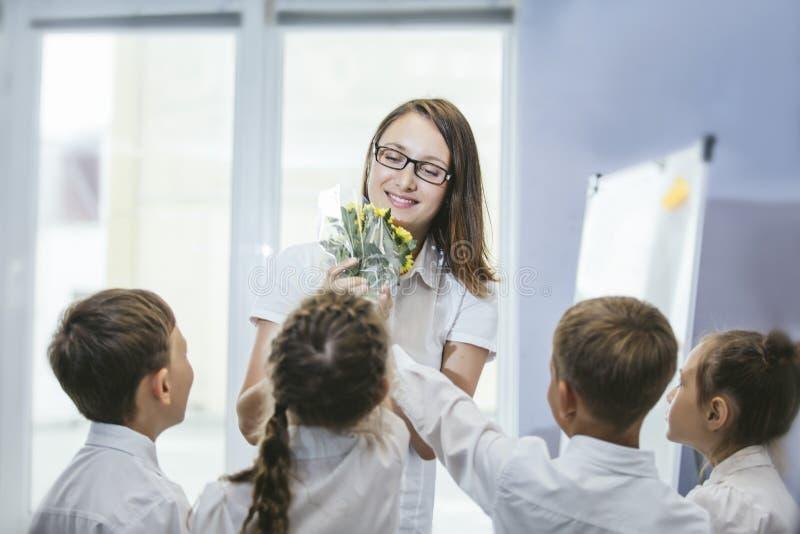 漂亮的孩子有花的小学生老师的 免版税库存照片