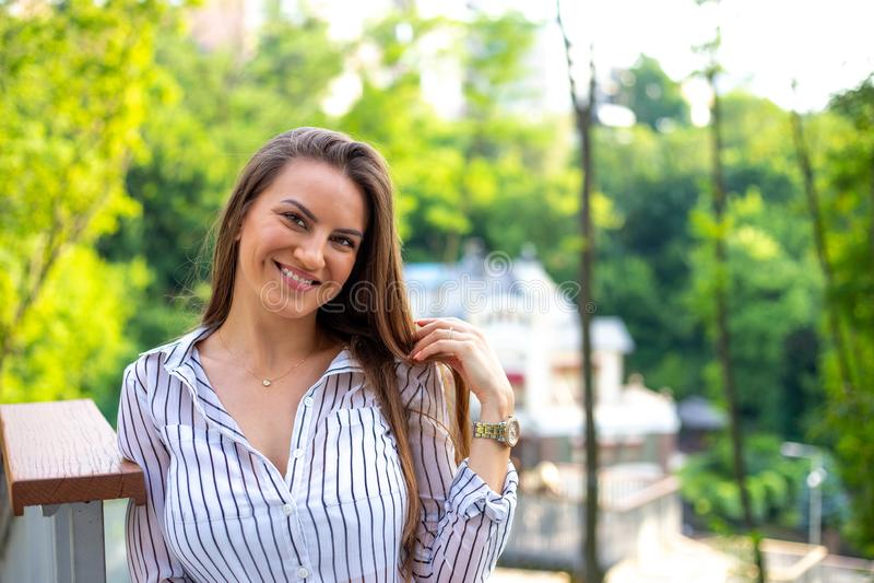 漂亮的成功女子,穿白色条纹衬衫,站在户外,周围环绕着漂亮的昂贵房子 图库摄影