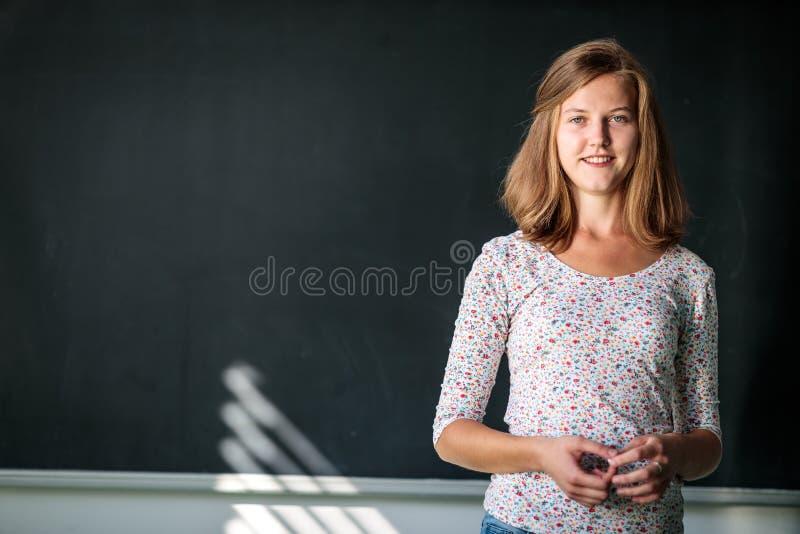 漂亮,年轻的女学生/年轻教师坐在黑板前 免版税库存图片