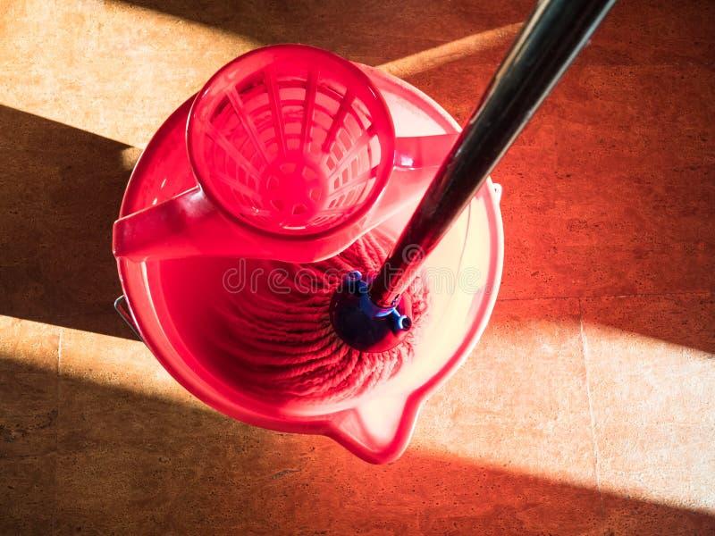 漂洗在红色桶的一个拖把水 免版税库存图片