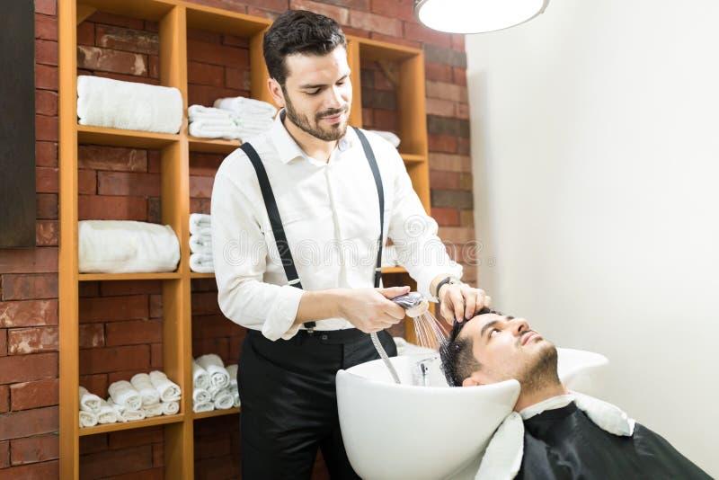 漂洗客户有喷水的美发师` s头发 免版税库存图片