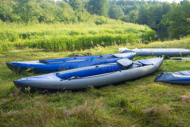 漂流的皮船沿河岸的河 小船或独木舟在河岸 免版税库存照片