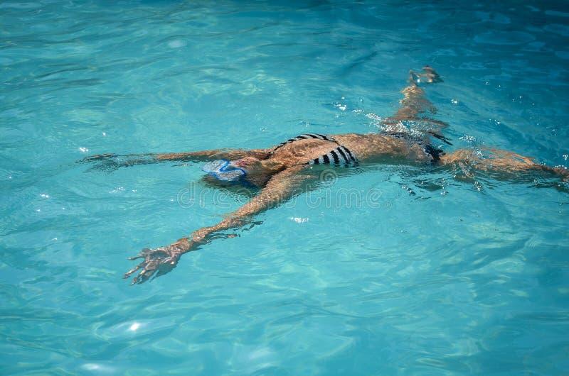 漂浮和游泳在水池水的少女 免版税库存照片