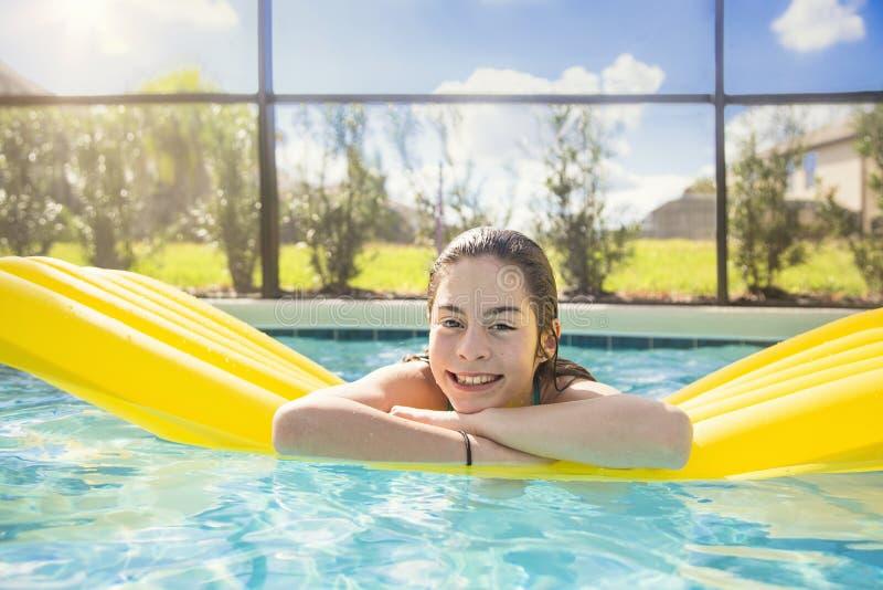 漂浮在一个室外游泳池的愉快的十几岁的女孩 免版税库存照片