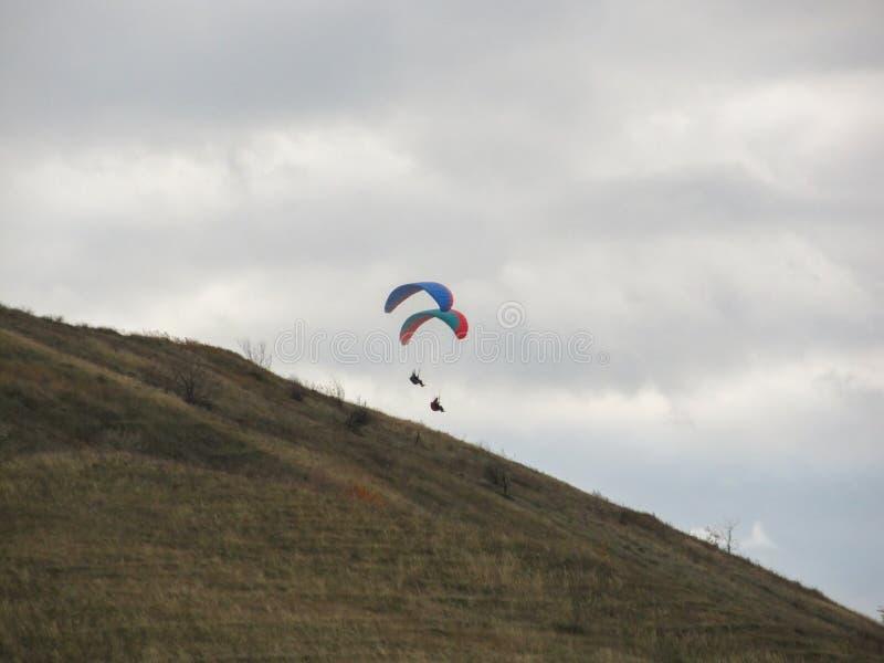 漂浮在一座高山上的天空中的两个滑翔伞 免版税库存照片