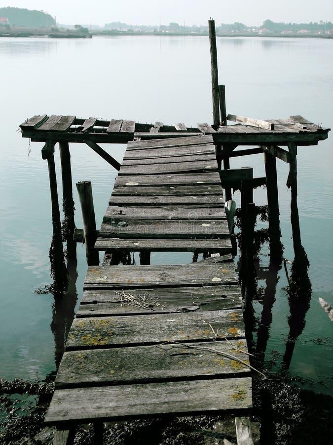漂浮在与出现在背景的镇的有雾的天气的老船坞 库存照片