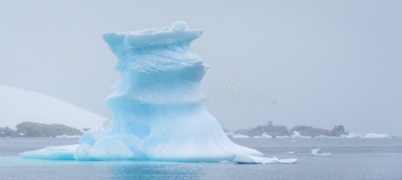 漂浮在南极州的美丽的土耳其玉色冰山,反对与研究工作站的有雾的背景 库存照片