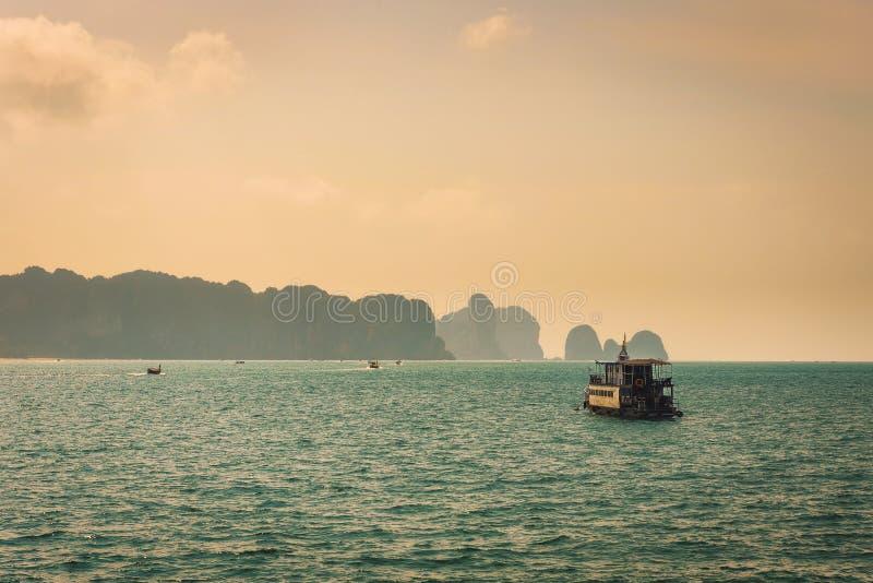 漂浮在发埃发埃海岛之间峭壁的泰国小船  免版税库存照片