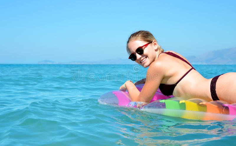 漂浮在可膨胀的床垫的女孩在海 图库摄影