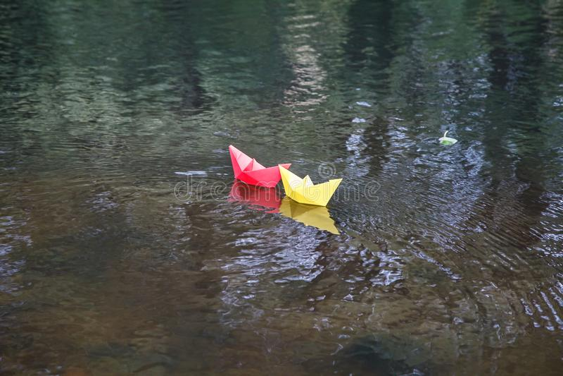 漂浮在小河的两条多彩多姿的纸小船 免版税库存图片