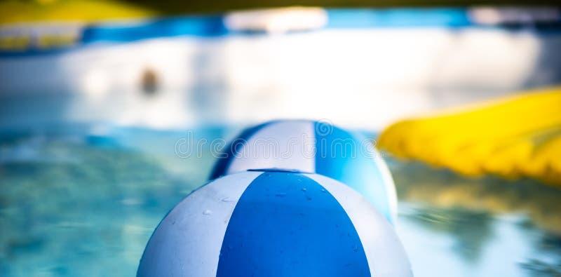 漂浮在房子庭院游泳场的可膨胀的五颜六色的球,有可膨胀的黄色床垫的在背景中 ?? 免版税图库摄影