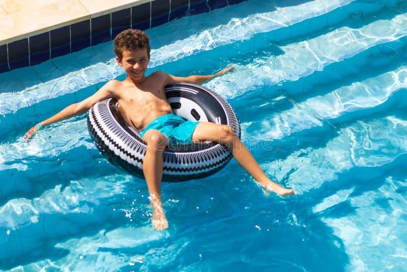 漂浮在水池的一个可膨胀的圈子的男孩 免版税库存照片