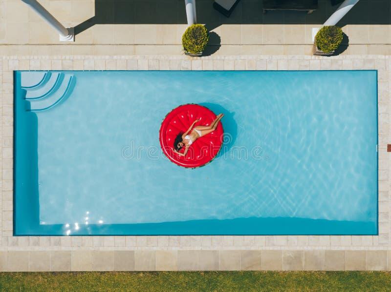 漂浮在水池的可膨胀的床垫的妇女 图库摄影