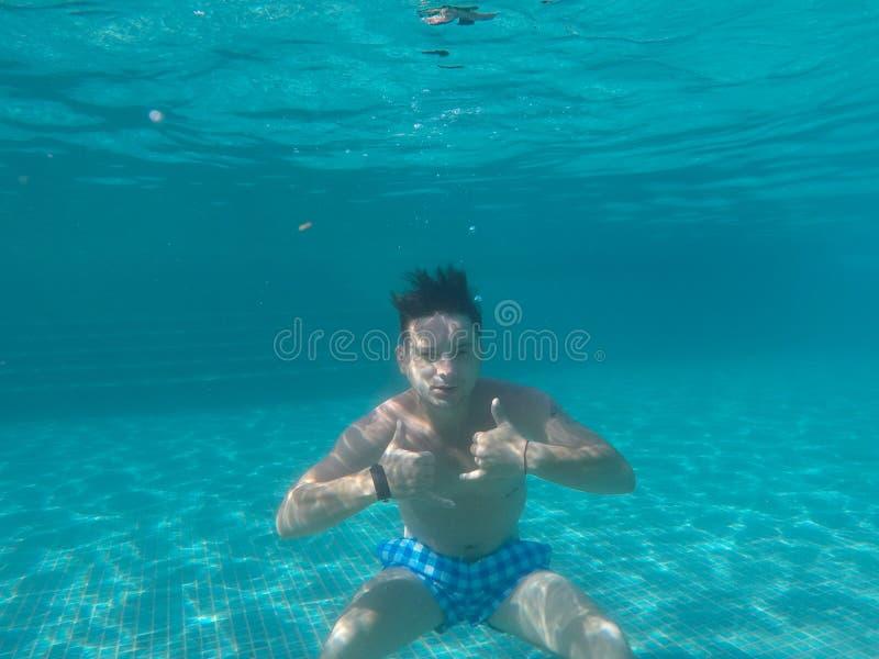 漂浮在水池的水下的一个人 库存图片