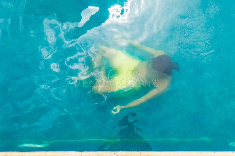 漂浮在水面下在游泳池的一个年轻人的顶视图 免版税图库摄影
