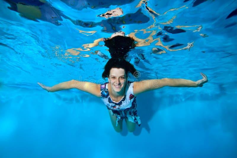 漂浮在水面下在蓝色背景的水池的礼服的一个美丽的女孩与她实施对边,看 免版税库存照片