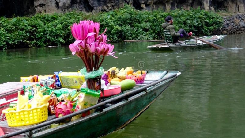 漂浮在河的小船运载的花 免版税库存照片