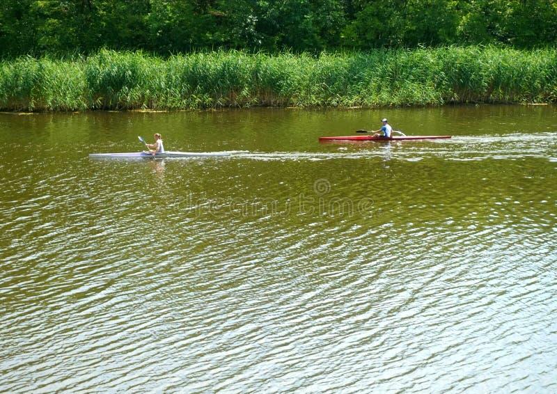 漂浮在沿河的皮船的夫妇反对潮流 免版税库存照片