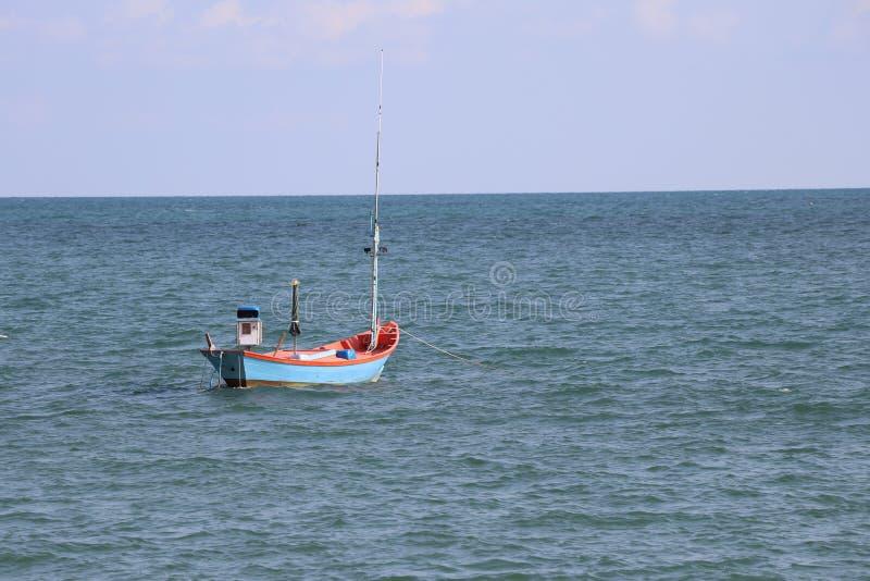 漂浮在海的渔夫的小船 免版税库存照片