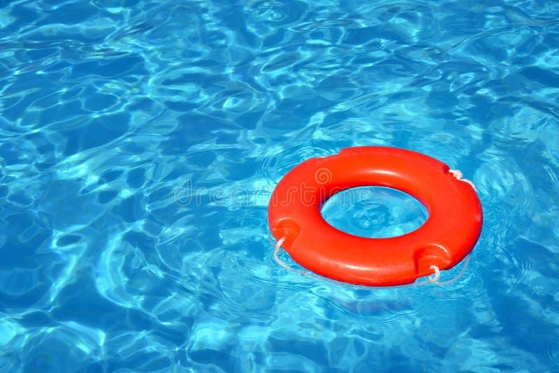 漂浮在游泳场的五颜六色的救生员管 免版税库存照片