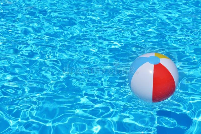 漂浮在游泳池的五颜六色的可膨胀的球 免版税库存图片