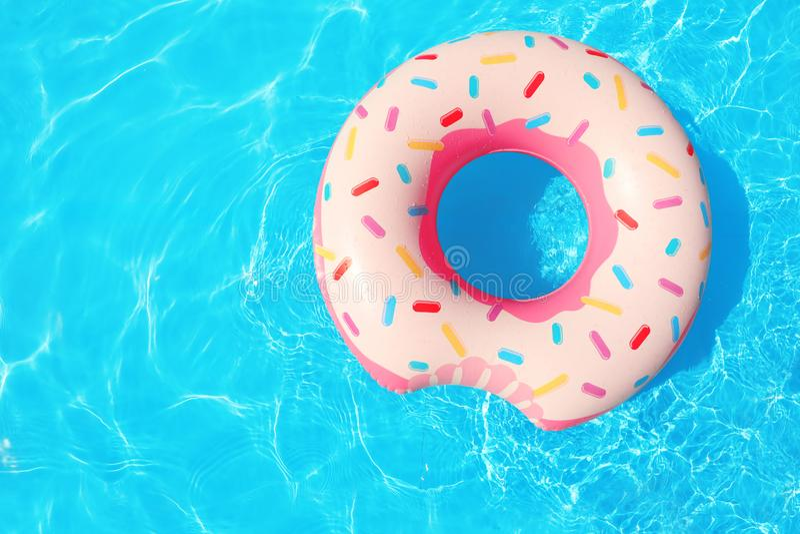 漂浮在游泳池的可膨胀的圆环在晴天 免版税图库摄影