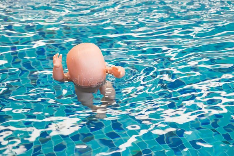 漂浮在游泳池,孩子d的危险的娃娃 免版税库存照片