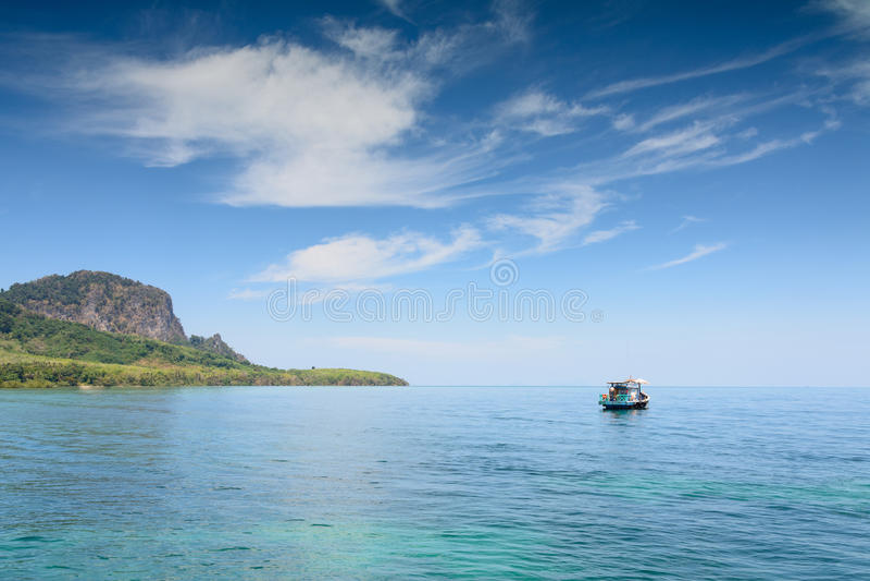 漂浮在热带海的地方渔夫小船在海岛附近 免版税库存照片