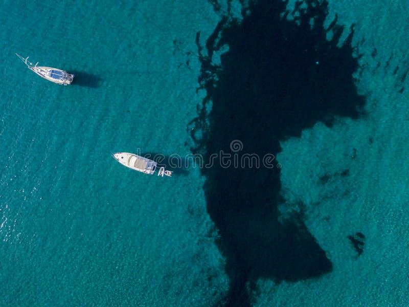 漂浮在透明海的被停泊的小船鸟瞰图  可西嘉岛 法国 免版税库存照片