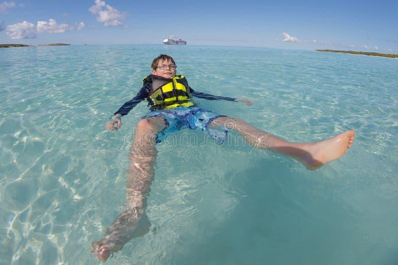 漂浮在透明的大海的救生衣的年轻男孩与游轮在背景中 库存图片