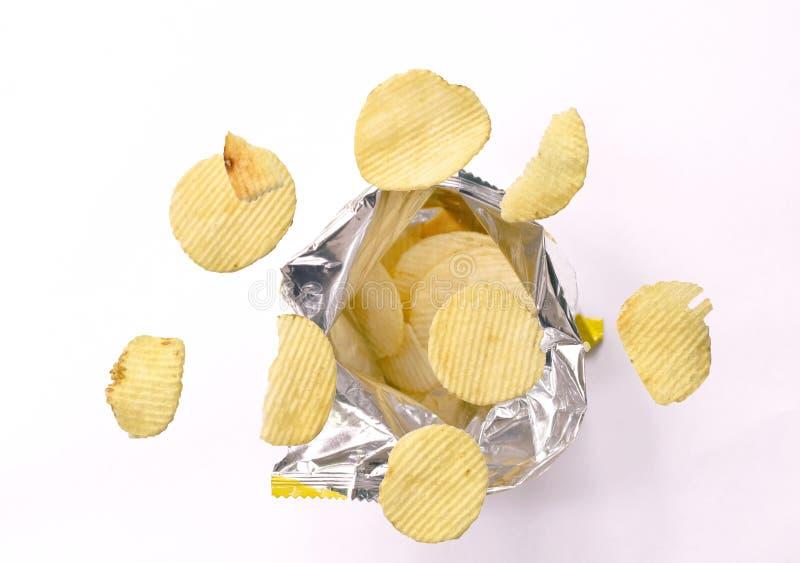 漂浮在铝芯的薯片包装在白色背景 免版税库存图片