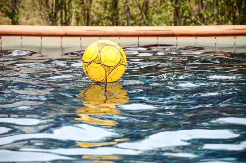 漂浮在水池的黄色五颜六色的海滩球 库存照片