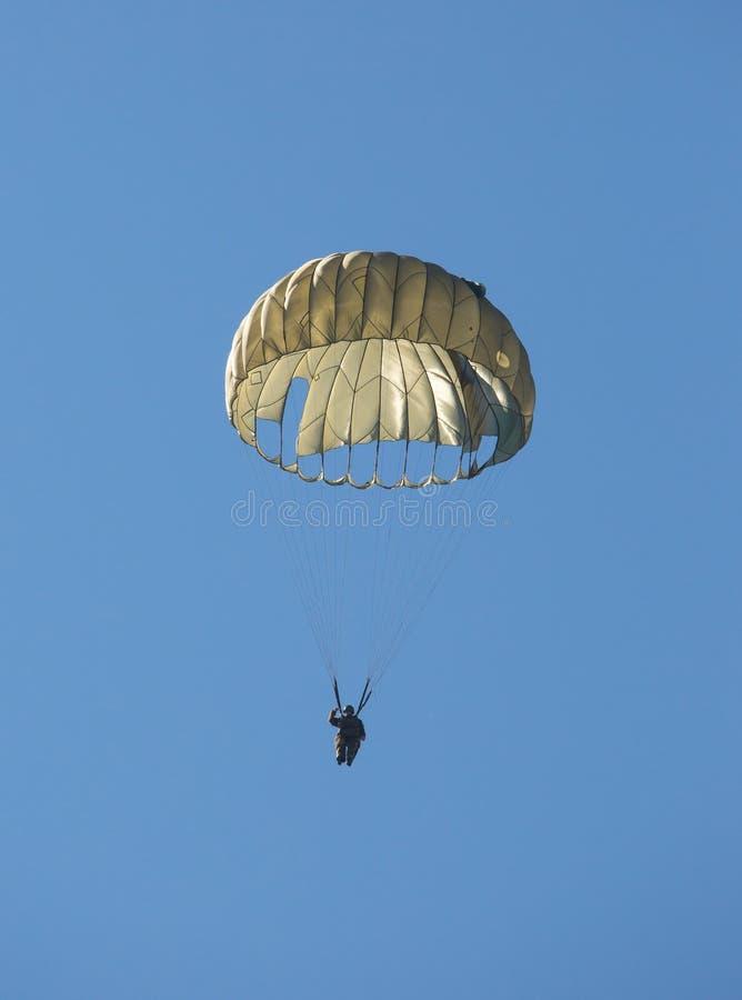 漂浮对地面的军队伞兵在降伞下 免版税库存照片