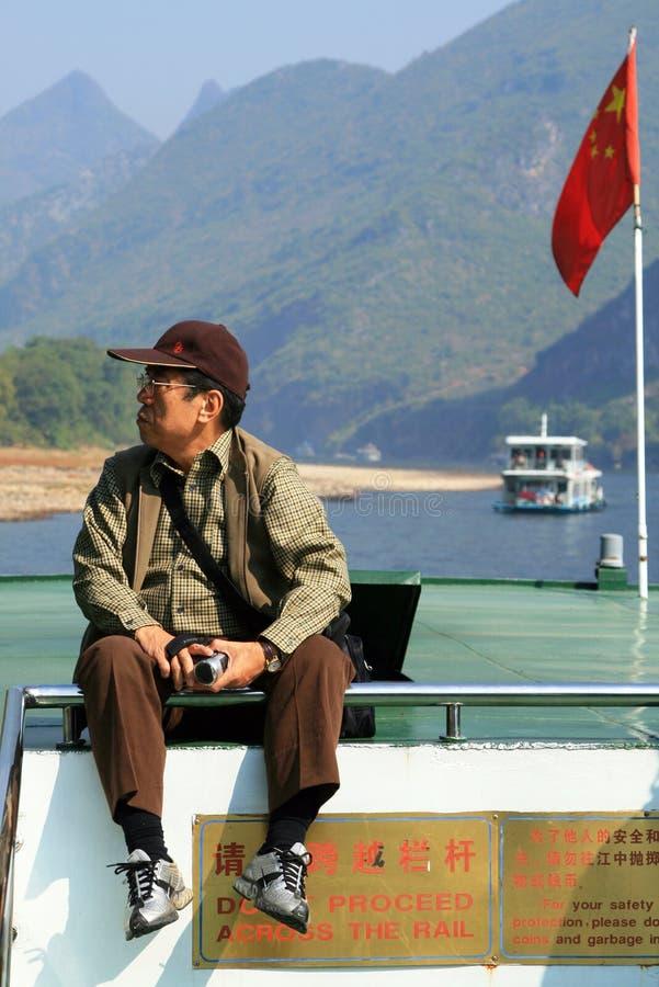 漂浮由风景李河的小船的中国游人 内在旅游业是非常普遍的在中国 免版税库存照片