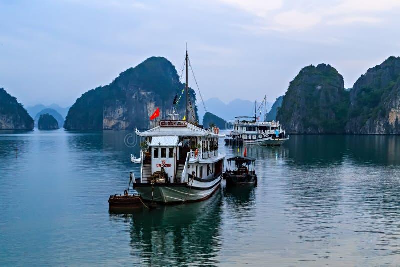 漂浮石灰石岩石下龙湾的游船旅游破烂物在越南 库存图片