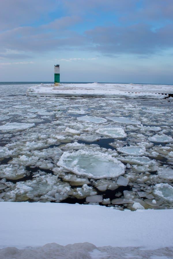 漂移在与灯塔的冰冷的水中的冰山在背景中 免版税库存照片